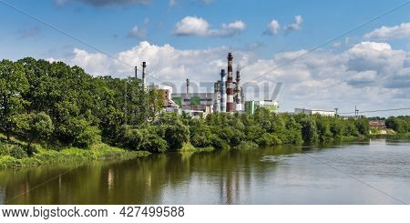 Pipes Of Woodworking Enterprise Plant Sawmill Near River. Air Pollution Concept. Industrial Landscap