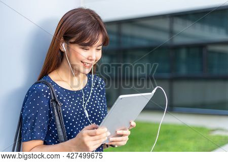 Young Attractive Asian Woman Reading The News From Her Computer Tablet While Using Earphones To List