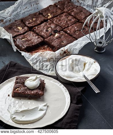 Brownie With Ginger, Dark Chocolate Coloured, Cut Into Equal Squares On The Gray Table. A Piece Of B