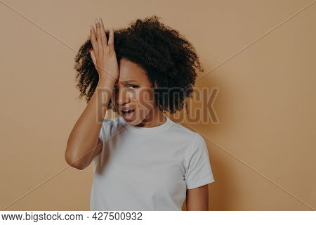 Studio Shot Of Young Stressful African Woman With Hand On Forehead Suffering From Strong Headache Or