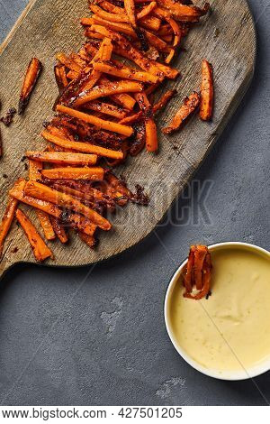 Sliced Caramelized Carrots With Bowl Of Parmesan Lie On A Cutting Board. Top View
