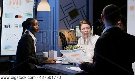 Diverse Multi-ethnic Businesspeople Discussing Company Strategy Analyzing Paperwork Statistics. Focu