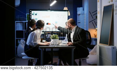 Diverse Business Teamwork Of Entrepreneur Analyzing Management Strategy Working In Office Room Late