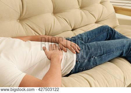 Man Suffering From Pain In Lower Right Abdomen On Sofa At Home, Closeup. Acute Appendicitis
