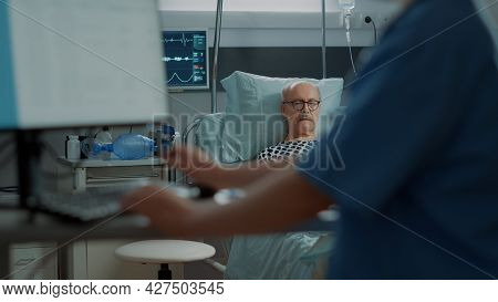 Nurse Talking To Sick Old Patient In Hospital Ward At Unit About Medical Health Problems And Disease
