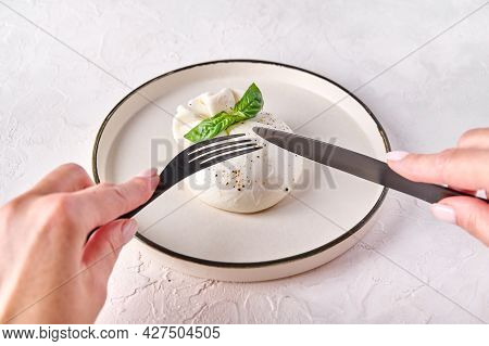 Close Up Womens Hands Cut With Black Knife And Fork Burrata Cheese With Basil On Light Plate