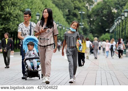 Moscow, Russia - July 2021: Asian Couple With Kid Girl And Baby Pram Walking On A Street On Crowd Of