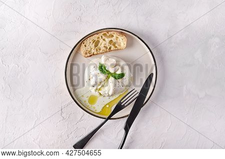Italian Cut Burrata Cheese With Ciabatta Bread And Olive Oil On White Plate With Black Knife And For