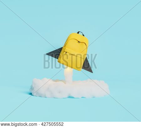 Yellow Backpack In The Shape Of Rocket Taking Off With Illuminated Ignition Cloud. Concept Of Educat