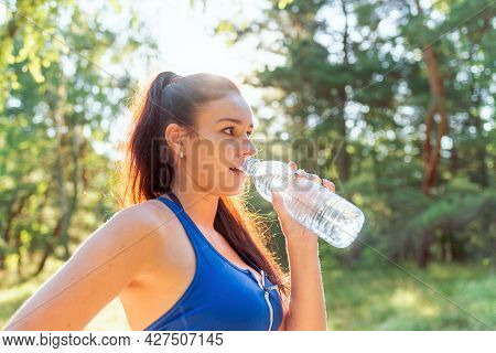 Pretty Girl Drinking Water From Bottle In A Forrest Or Park.portrait Of Beautiful Sporty Woman Drink