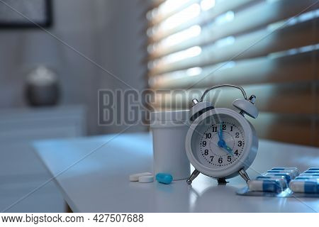 Alarm Clock And Pills On White Table Indoors, Space For Text. Insomnia Treatment