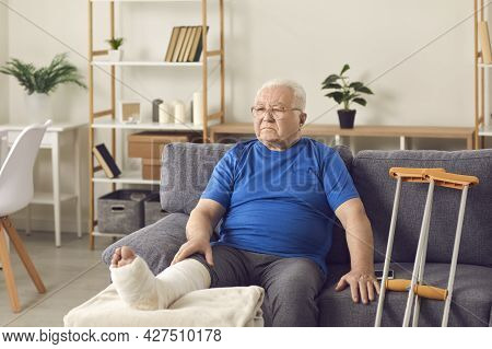 Disappointed Senior Mature Man Sitting On Sofa With Broken Leg In Cast