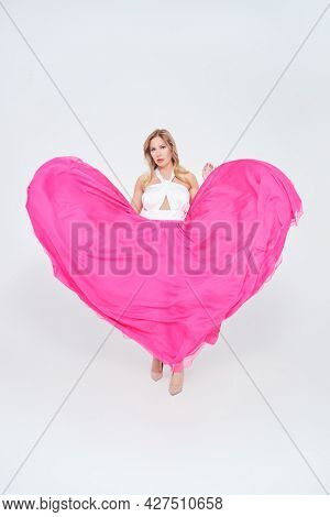 Gorgeous middle-aged woman in a lush evening dress on a white background. Evening fashion. Full length studio portrait.
