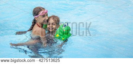 Banner With Happy Brother And Sister Swim In The Pool. Smiling Girl And Boy Are Playing In The Pool.