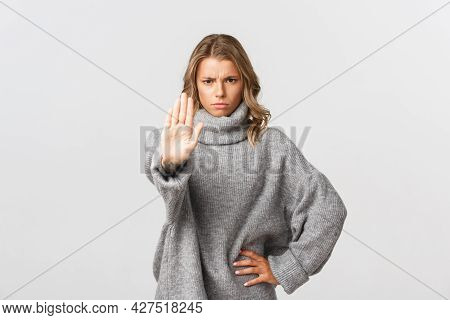 Serious Confident Woman In Grey Sweater, Extend One Arm And Telling To Stop, Prohibit Action, Frowni