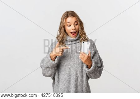 Portrait Of Attractive Caucasian Female Model In Grey Sweater, Looking Amazed And Pointing At Mobile
