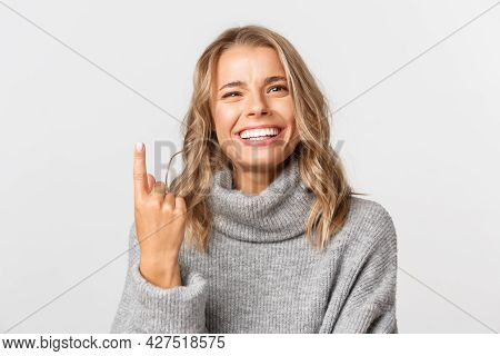Close-up Of Carefree Blond Girl In Grey Sweater, Showing One Finger And Smiling, Standing Over White