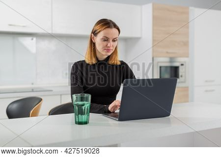 A Girl With Blond Hair In A Black Blouse Sits At Home In The Kitchen And Works Behind A Laptop. Remo