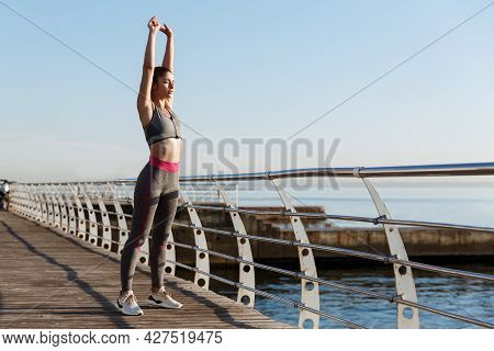 Young Fit Sportswoman Stretching Before Morning Exercises. Female Runner Workout On Seaside Promenad