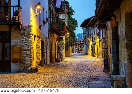 Narrow Alley Of Old Stone Town With Cobbled Streets Illuminated At Night.