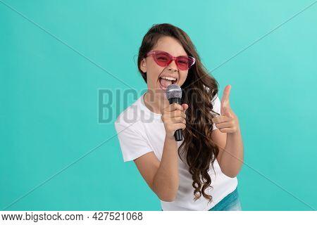 Happy Girl Singer Point Finger Gun Singing Song To Microphone Blue Background, Karaoke