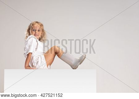 Side View Portrait Of Little Cute Smiling Caucasian Girl Sitting On Large Box Isolated Over White St
