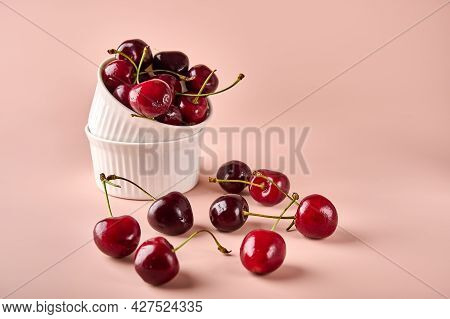 Ripe Red Wet Cherry In White Bowl And Next To It On Powdery Pink Background. Copy Space For Text