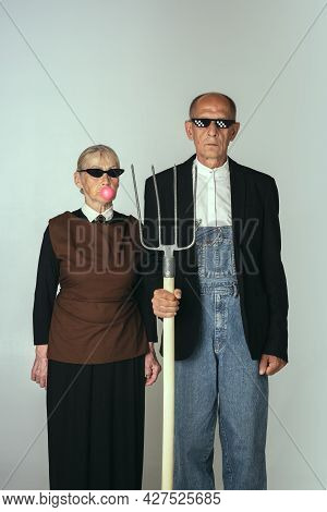 Elderly Man And Woman In Art Performance, Replica Of Painting American Gothic. Retro Style, Comparis