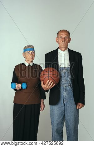Portrait Of Elderly Man And Woman In Art Performance, Replica Of Painting American Gothic. Retro Sty