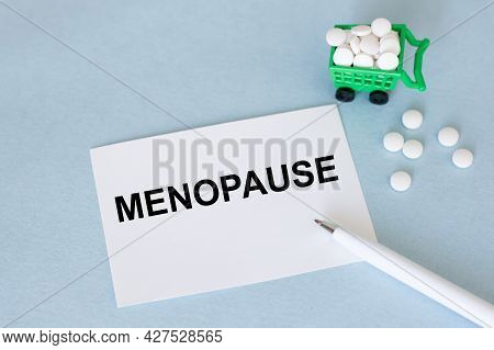 On The Card Is The Text Of Menopause On A Blue Background Next To A White Pen And White Pills