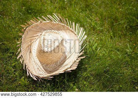 Farmer's Yellow Straw Hat In The Grass. Cowboy Straw Hat. Rural Symbol.
