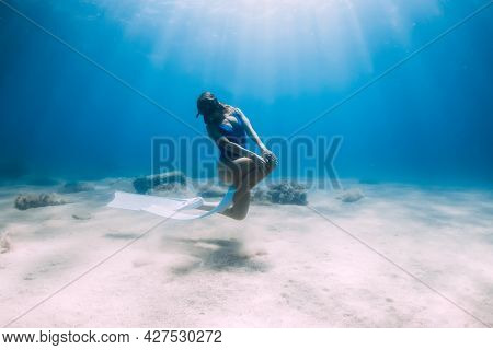 Female Free Diver With Fins Posing Underwater In Blue Sea With Sunlight.