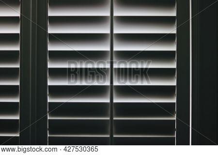 Full Frame Monochrome Image Of Light Shining Through Plantation Shutters