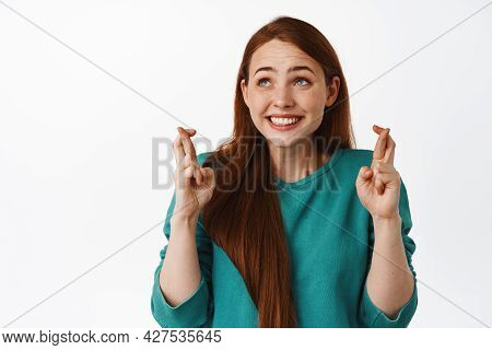 Cute Hopeful Redhead Woman Cross Fingers For Good Luck, Smiling And Anticipating News, Looking Aside