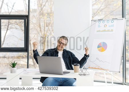 A Man Dressed In Casual Clothes Works In The Office With A Laptop And Expresses Positive Emotions