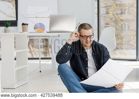A Man Dressed In Casual Style Works In The Office And Looking Through Business Papers