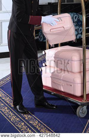 The Doorman Puts The Suitcases On The Trolley. Doorman In Uniform. Unrecognizable Person. Meeting Gu