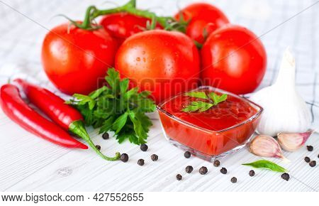 Ripe Tomatoes And Homemade Ketchup On The Table. The Concept Of Cooking Sauce Or Ketchup. Close-up.