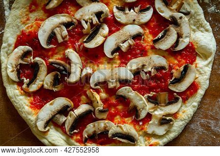 Raw Italian pizza known as the Margherita. Yeast dough pizza with mushrooms, mozzarella cheese and tomato sauce.