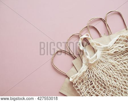 Biodegradable Paper Bags And Reusable Mesh Cotton Shopper On Neutral Light Pink Background. Eco Frie