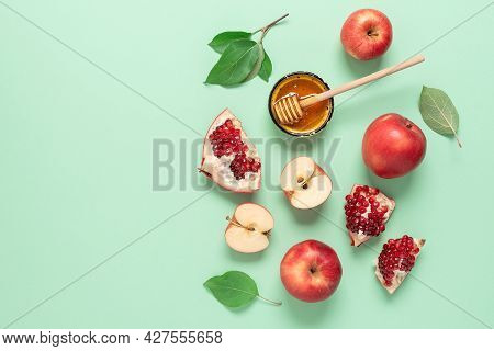 Apples, Pomegranate And Honey On A Green Pastel Paper Background. Rosh Hashanah. Jewish New Year. Tr