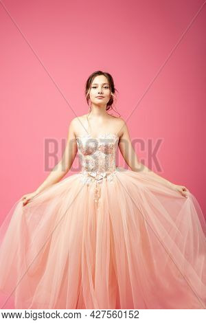 A Beautiful Woman Is Standing With Her Face And Holding A Lush Organza Skirt In Her Hands. A Young W