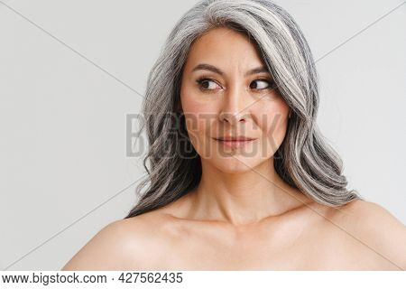 Mature shirtless woman with grey hair posing and looking aside isolated over white background