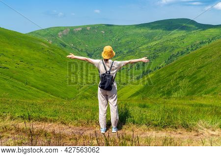Girl Traveler With A Backpack Stands With Her Arms Outstretched In The Mountains In Summer. The Top