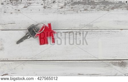 Key and house shaped keychain arrangement on old white wood  background. Top view, flat lay. Real estate, insurance concept, mortgage, buy sell house, realtor concept