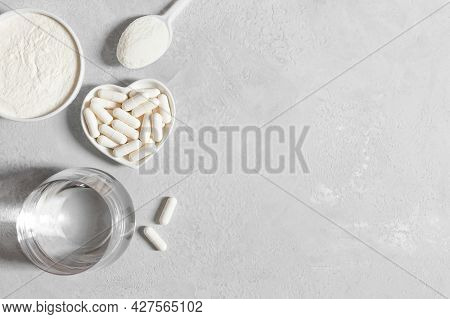 Collagen Supplement. Collagen Powder And Capsules On A Gray Background. Healthy Skin And Bones Conce