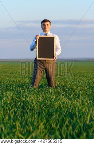 businessman holds a blackboard with an empty space and poses on a green grass field - business concept