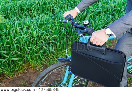 Businessman's hand with briefcase and a bicycle in a green grass field - business concept for freedom, vacation or freelance. Beautiful spring nature.