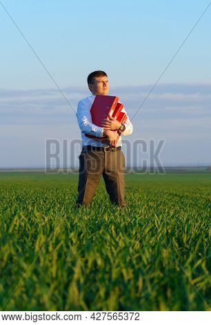 businessman holds an office red folder with documents in a green grass field - business concept