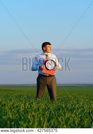 a businessman holds an office clock and red folder in a field with green grass - business and time concept